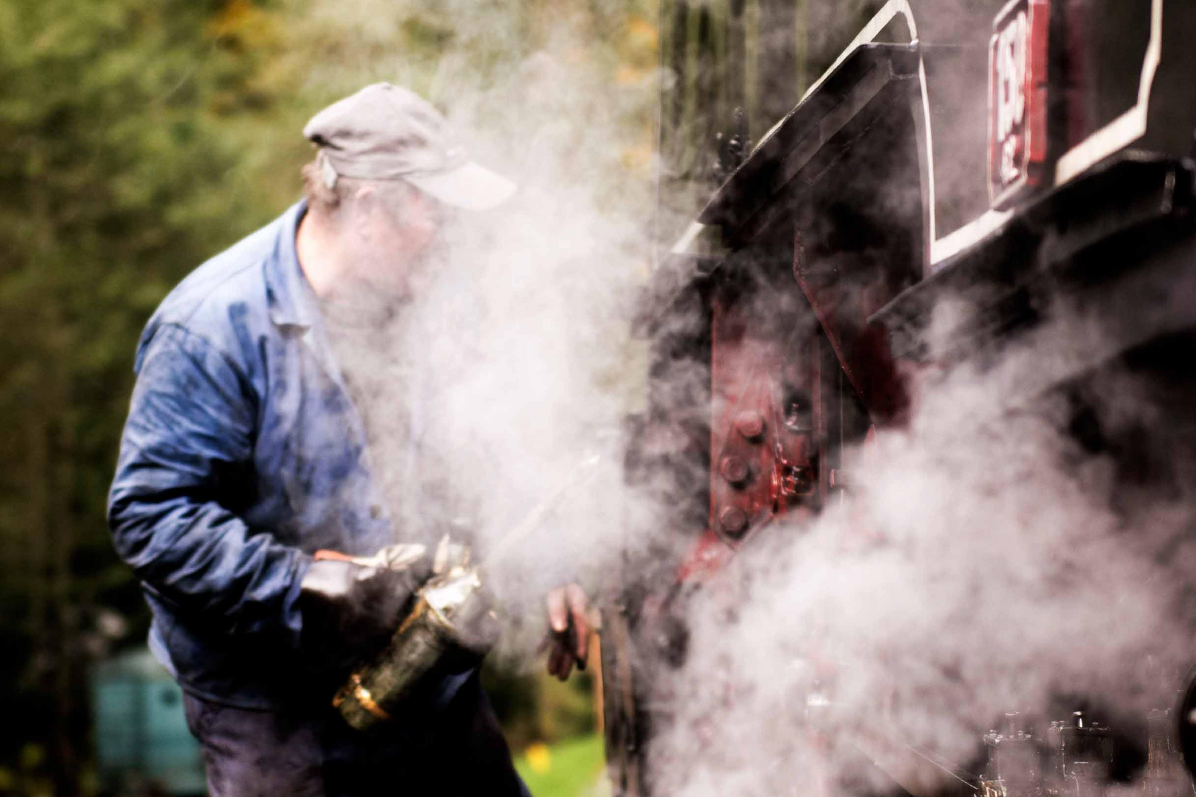 Man works on side of train in cloud of steam