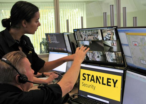STANLEY Security employees look at camera monitors