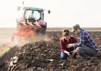 Two people look at dirt in field with tractor behind